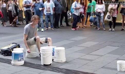 バケツでストリートドラムをする男性